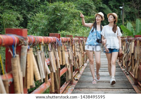 group of japanese female best friends walk on wish wood bridge with bamboo tube for Wishing at pingxi taipei taiwan. young girl point blue sky showing sister in beautiful nature forest across river. #1438495595