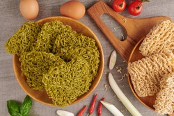 Group of Japanese style green noodles, Mendake, uncooked instant vegetable or crispy dry jade noodles on wooden chop board. Fast cooking menu. Traditional noodles, Raw food ingredient.  Food concept.