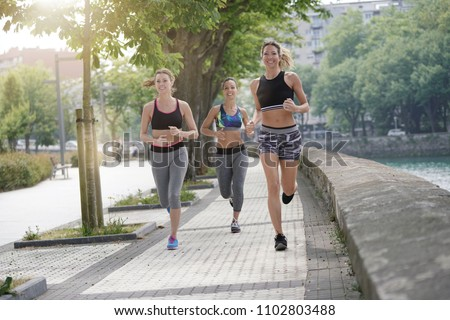 Group of joggers running in town #1102803488