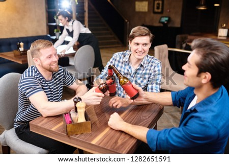 Group of jolly excited young male friends in casual clothing sitting at table in bar and toasting with beer bottles while having fun on Friday #1282651591