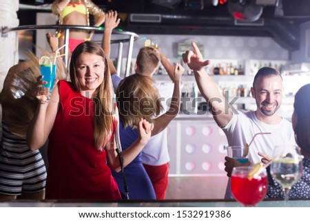 Group of joyful people clubbing in the night club with drink