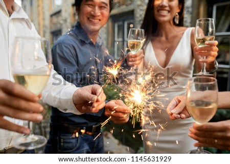 Group of joyful people drinking champagne and burning Bengal lights at great wedding party #1145631929