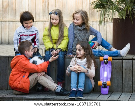 Group of junior school children joyfully chatting and smiling outdoors #1037105701