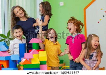 Group of kids and their female teacher screaming happily, having fun at kindergarten. Happiness, daycare, education concept