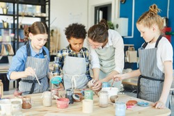 Group of kids and their teacher leaning over table with gouahes and painting self-made clay items