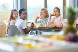 Group of kids as friends having lunch in school cafeteria
