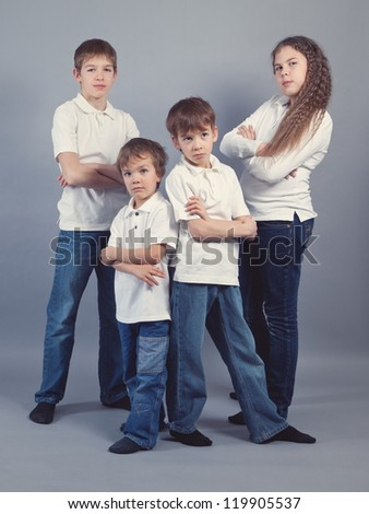 Group of kids in jeans on gray background, studio
