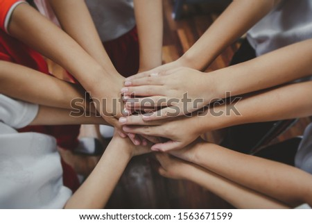 Group of kids joining  hands Together , Team work or unity Concept #1563671599