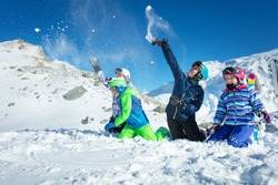 Group of kids play in snow throwing snowballs in ski outfit playing fun game together