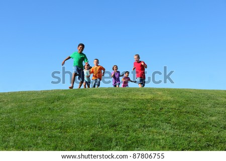 Group of kids running on grass hill with blue sky - stock photo