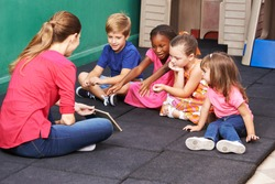 Group of kids talking about book with nursery teacher in preschool
