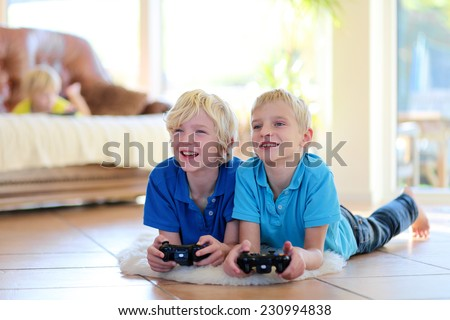 Group of kids twin teenage brothers having fun after school day playing video game holding joysticks in hands lying cozy on tiles floor on warm lambskin in bright sunny living room with big windows