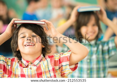 Group of kids with books on heads smiling in classroom