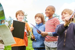 Group of kids with clipboards on scavenger hunt in nature at children's birthday party