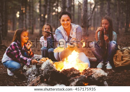 Group of kids with mom sitting by the fire and drinking tea in autumn forest, hike at weekend - stock photo