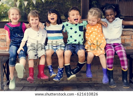 Group of kindergarten kids friends arm around sitting and smiling fun