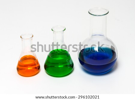 Group of laboratory flasks empty or filled with a clear liquid on white background.