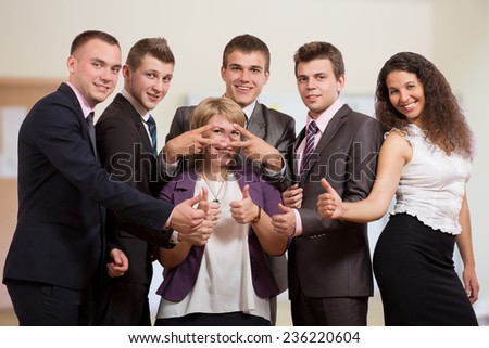 Group of laughing business people. Six business people make funny gestures. The stay inside of office interior and dressed according to business dress code.