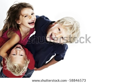 Group of laughing children hugging each other and looking up, isolated on white background with copy-space, top view. - stock photo