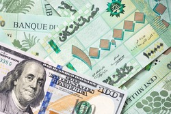 Group of 100 000 Lebanese pounds bills and 100 US dollar bill