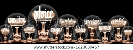 Group of light bulbs with shining fibers in a shape of Advice, Consulting, Knowledge and Experience concept related words isolated on black background; horizontal composition Foto stock ©