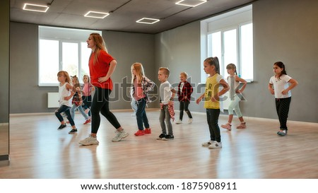 Group of little boys and girls dancing while having choreography class in the dance studio. Female dance teacher and children. Contemp dance. Hip hop. Kids and sport. Full length