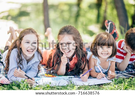 group of little girls and boy painting with paintbrush and colorful paints #716638576