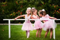 Group of little girls doing ballet bar exercises at beautiful summer garden background