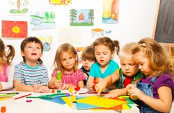 Group of little kids painting with pencils and gluing with glue stick on art class in kindergarten