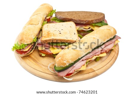 group of long baguette and toasted sandwiches with lettuce, vegetables, salami, ham and cheese on a cutting board isolated on white