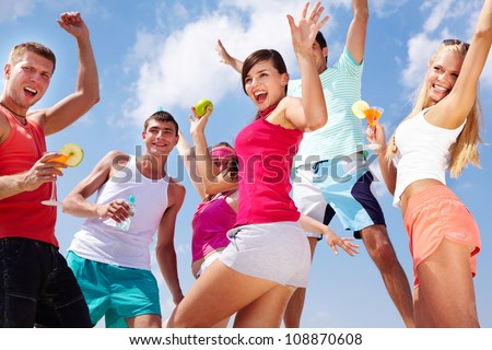 Group of lovely young people dancing and jumping outdoor