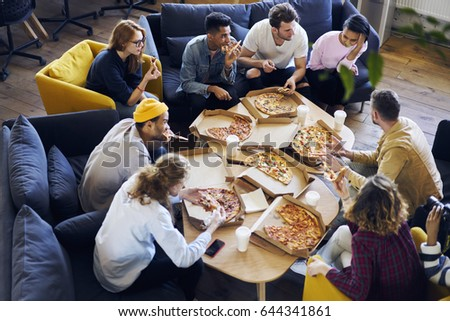 Group of male and female coworkers having  lunch break eating pizza together in office, overhead shot of young casually dressed staff members recreating after finishing tasks making fast snack