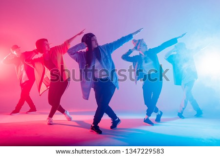 Group of male and female dancers in colorful neon light having fun dancing. Party guests enjoy atmosphere and effects in the night club. Creative fashionable neon color.