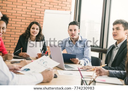 Group of male and female Millennial business associates at teamwork meeting listening attentively to colleague giving presentation #774230983
