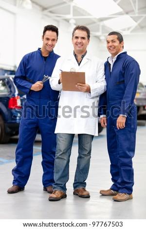 Group of male mechanics smiling at a car repair shop