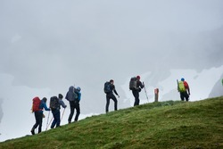 Group of male tourists with backpacks climbing grassy hill. Brave alpinists walking uphill in mountains with foggy cliff on background. Concept of hiking, travelling, mountaineering and backpacking.