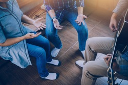 Group of  man and woman friends sitting on wooden chair while praise and worship God  by playing guitar and sing a song together in home office, Christian background small fellowship meeting concept.