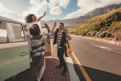 Group of man and women on road trip standing by the van and giving high five. Cheerful friends enjoying themselves on a vacation.
