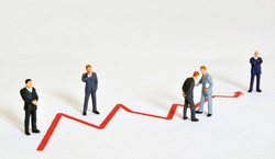 Group of managers (model railroad figures) positioned around graph showing rising business development.