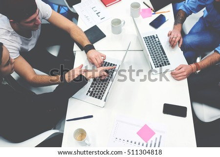 Group of marketers gathered for a briefing on the creation of a new design for the company's product. Business people working on laptops in modern coworking office. Successful startup of young team #511304818