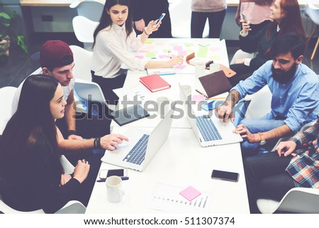 Group of marketers gathered for a briefing on the creation of a new design for the company's product. Business people working on laptops in modern coworking office. Successful startup of young team #511307374