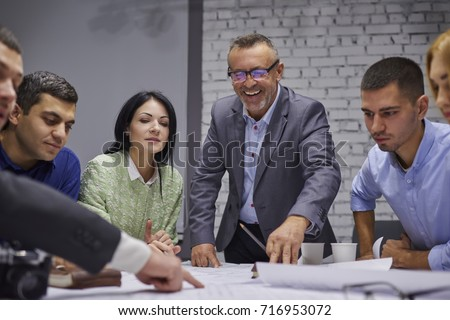 Group of marketing experts dressed in formal wear developing advertising campaign while collaborating in office.Crew of creative designers discussing ideas and sharing opinions during work process
