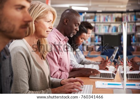 Group Of Mature College Students Working On Computers In Library