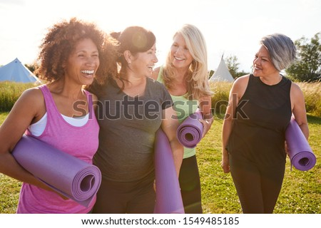 Photo of Group Of Mature Female Friends On Outdoor Yoga Retreat Walking Along Path Through Campsite