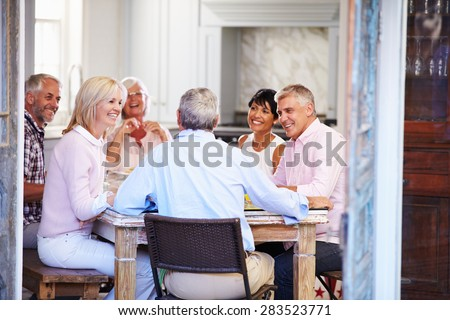 Group Of Mature Friends Enjoying Meal At Home Together