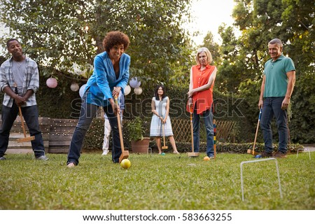 Group Of Mature Friends Playing Croquet In Backyard Together #583663255
