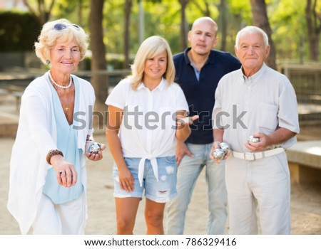 Group of mature friends playing petanque in park outdoor