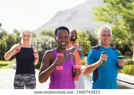 Group of mature happy people using dumbbells for workout session. Multiethnic group of smiling women and senior men exercising with dumbbells outdoor. Seniors doing workout and looking at camera.
