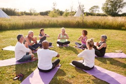 Group Of Mature Men And Women In Class At Outdoor Yoga Retreat Sitting Circle Meditating
