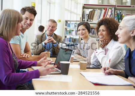 Group Of Mature Students Collaborating On Project In Library #284521556